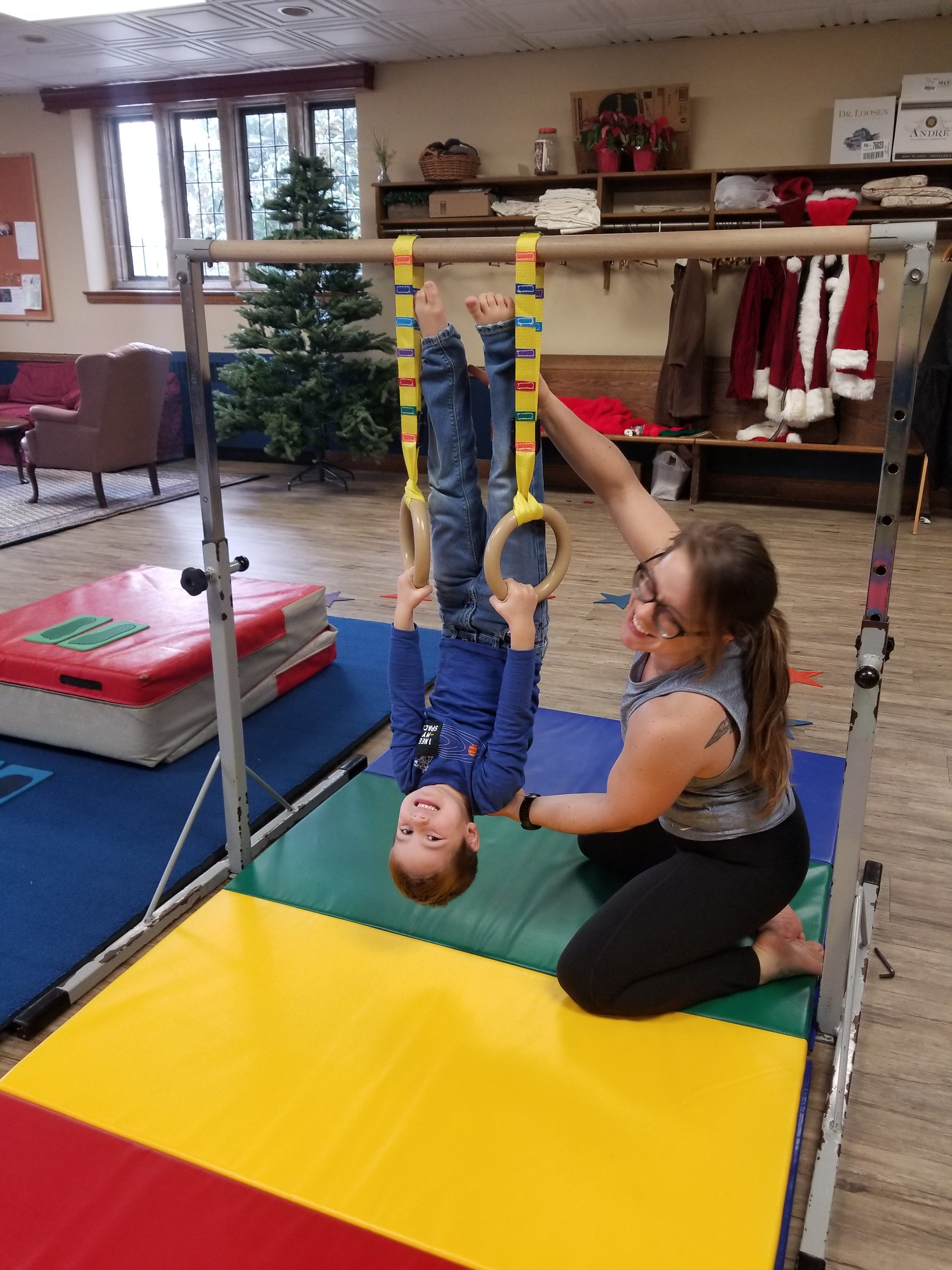 Instructor Katie helping a child with gymnastic rings